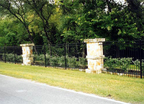 3 rail black metal steel fence around property stone pillars