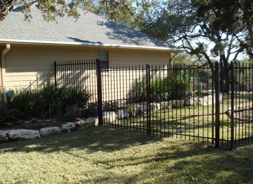 black iron fence around backyard of home