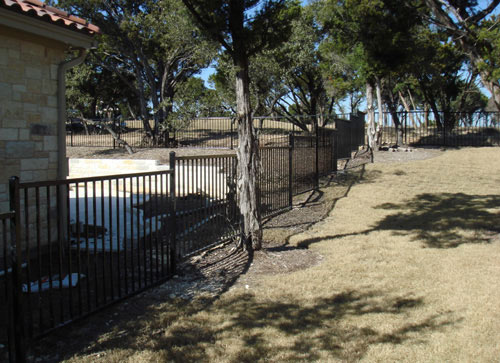black metal fence around pool in backyard