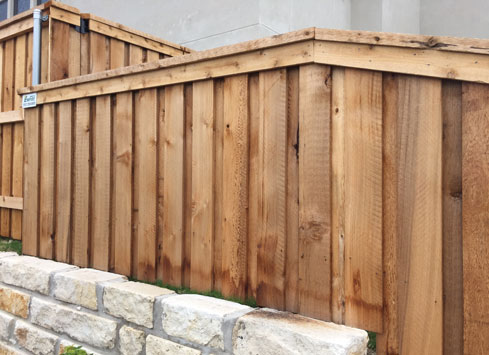 cedar privacy fence with cap and trim on stone wall