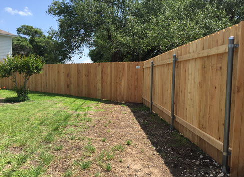 simple backyard fence with metal fence posts