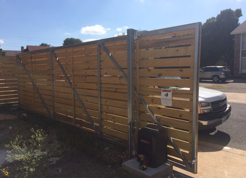 tall front yard fence with metal frame and automatic gate