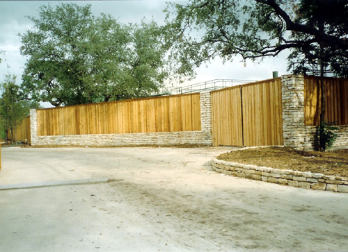 wood fence with stone wall around driveway