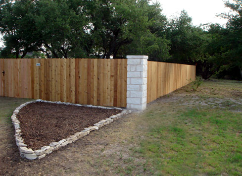 wood privacy fence with stone corner posts